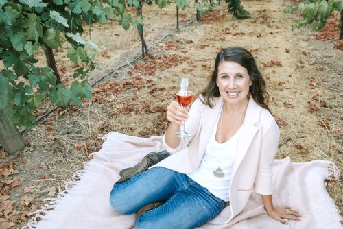 Amista Vineyards Winemaker Ashley sitting among the vines on a blanket with a glass of sparkling rose wine