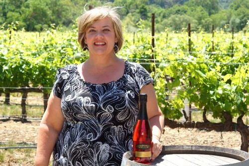 Amista Vineyards Tasting Room Manager, Tammy standing next to wine barrel with bottle of Sparkling Syrah in the Syrah vineyard