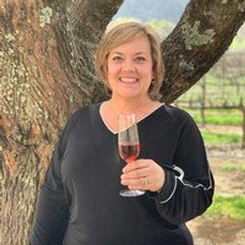 Amista Vineyards Tasting Room Manager, Tammy, holding a glass of Sparkling Syrah, standing by a tree with the Syarh vineyards in the background.
